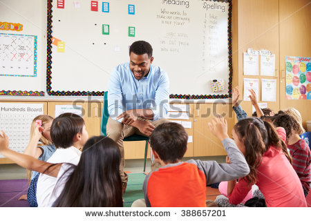 stock-photo-elementary-school-kids-sitting-around-teacher-in-a-classroom-388657201